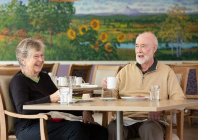 Elderly couple having a laugh together in the dining hall