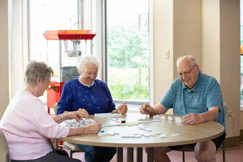 residents enjoying dominoes in the game room